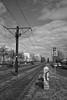 Berlin, Falkenberger Chaussee (tom-schulz) Tags: x100f rawtherapee haldclut monochrom bw sw urban berlin thomasschulz perspektive stromkasten schild schienen hochhaus himmel wolken