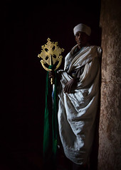 Portrait of an ethiopian orthodox priest holding a cross in the darkness of a cave church, Amhara region, Lalibela, Ethiopia (berengere.cavalier) Tags: 1people abyssinia adult adults africa african bible blackethnicity blackpeople blackskin cavechurch christian christianity church civilization color cross dark darkness day devotion eastafrica ethio1683 ethiopia ethiopian faith fulllength geez gez halflight holy hornofafrica indoor indoors lalibela men monastery monk old oldmen onemanonly oneperson onlymen orthodox orthodoxchurch pilgrim pilgrimage pray praying priest religion religious rockchurch senior seniormen shadow spirituality tradition traditional unesco vertical worldheritage worldheritagesite amhararegion