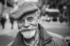 Happiness Is... (Leanne Boulton) Tags: portrait urban street pose posed portraiture spontaneous streetphotography streetportrait eyecontact streetlife old man male face eyes smile smiling expression happy happiness mood emotion feeling beard moustache goatee style stylish cap tone texture detail closeup depthoffield bokeh naturallight outdoor light shade city scene human life living humanity society culture people canon canon5d 5dmkiii 70mm ef2470mmf28liiusm black white blackwhite bw mono blackandwhite monochrome glasgow scotland uk