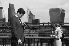 Text in the city.... (markwilkins64) Tags: chemistry railings cranes bright sunny lunchtime texting candid text mobilephone woman man thames architecture millenniumbridge london monochrome mono blackandwhite white black street streetphotography england uk