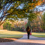 A student walks across the Court of North Carolina on NC State's North Campus.