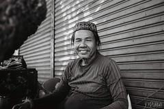 Street Portrait #1 (D. R. Hill Photography) Tags: bangkok thailand thai asia southeastasia street streetphotography streetportrait portrait face man environmentalportrait monochrome blackandwhite city urban hat contax contaxg1 g1 kodak kodakfilm kodaktrix400 trix trx400 carlzeissplanar35mmf2 planar 35mm 135 35mmfilm analog film