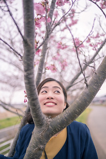 Happy young woman making funny face between branch