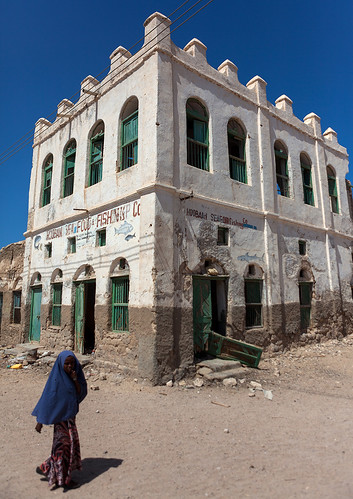 Somali woman passing in front of  former ottoman empire house, North-Western province, Berbera, Somaliland
