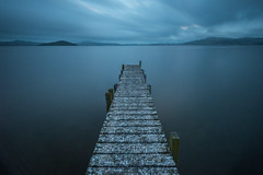 Walkway to the storm (Nikhil Ramnarine) Tags: newzealand northisland rotorua lake pier jetti abandonded stromy clouds longexposure stormyclouds glasslake vignette mountain blue nightmare empty lonely