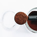 Top view of spoon with ground coffee