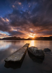 Skyfire (Pete Rowbottom, Wigan, UK) Tags: sunset landscape keswick lake water reflection derwentwater sunlight sun light warmth 2018 winter lakedistrictnationalpark pier jetty rocks mountains wideangle nikond750 dusk clouds outdoors dramatic beautiful cumbria england lakedistrict peterowbottom nikon1424f28 skyfire sunburst flare nisifilters catbells wainwright surreal waterreflections sky art detail remote tranquil peaceful serenity glow uklandscape britain goldenlight