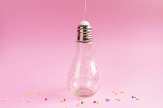 Stylish Big Bulb with lights inside on pink background. Colorful sprinkles