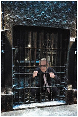 Smedley is behind bars. But, he's smiling broadly because on the other side of those bars is a bevy of a great vintner's private stock. (Fotofricassee) Tags: winery vintner grate bars private stock