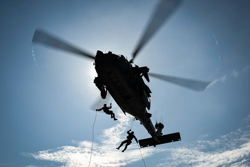 Sailors rappel from an MH-60S Sea Hawk helicopter to the flight deck.