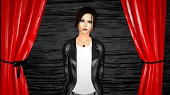 OCD Bait (alexandriabrangwin) Tags: alexandriabrangwin secondlife 3d cgi computer graphics virtual world photography symetrical shiny glossy red latex rubber curtains woodgrain black wall uneven wrong way round distance shifted smiling wry talking woman standing leather jacket pants white shirt silver nacklace