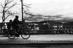 Grainy clouds over the city (stefankamert) Tags: stefankamert street clouds grain bicycle tree noir noiretblanc blackandwhite blackwhite people bike fence ricoh gr grd grdiv nopostprocessing