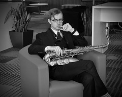 Serious... (tim.perdue) Tags: serious portrait candid iphone man person figure musician seated saxophone sax tenor musical instrument suit tie iphoneography mobile phone se iphonese greater columbus convention center gccc ohio downtown urban city glasses jazz music chair carpet plant