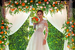 Bride holding flowers in hand (Hosting and Web Development) Tags: bride wedding flower leaf frame green white orange dress nikon stand arm face body smile eyes femininity female woman happy lights beautiful beauty portrait one person young indoor hand horizontal asia vietnam shoulder