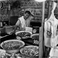 Where do I begin... (John Riper - AWAY FOR AWHILE) Tags: johnriper street photography straatfotografie square vierkant bw black white zwartwit mono monochrome thailand streetfood floating market candid john riper xt2 fujifilm 18135 amphawa food man seller bags stall vendor helpless crisis pickles