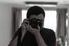 Self Portrait (D. R. Hill Photography) Tags: blackandwhite monochrome analog film kodak kodakfilm kodaktmax100 tmax 135 35mmfilm nikon nikonfe2 fe2 nikon50mmf18 nikon50mm 50mm primelens fixedfocallength manualfocus photographer selfportrait camera reflection