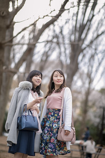 Young female friends looking above in public park