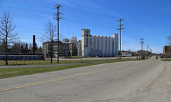 Stock's Mill — Hillsdale, Michigan (Pythaglio) Tags: hillsdale hillsdalecounty michigan stocksmill building structure mill silos concrete massive industrial industry field street utilitypoles wires cables bluesky
