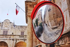 Malta Streets (Douguerreotype) Tags: people city street mirror buildings flag malta architecture red reflection