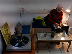 #S01 the mystery is in the clues (watcher330) Tags: carmarthen man cafe recordplayer newspaper