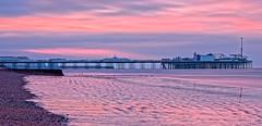 New Day (Geoff Henson) Tags: dawn sunrise sunset sky cloud beach sea coast seaside sand stones water ocean pier building structure fairground red pink seascape 1000v40f