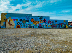 A Long Wall of Bubbles (Steve Taylor (Photography)) Tags: blowingbubbles bubble peace sam space mickymouse art graffiti mural streetart blue brown gravel kid child girl newzealand nz southisland canterbury christchurch newbrighton winter