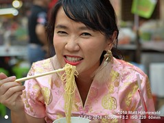 2015-12a You and Mee 2018 (08) (Matt Hahnewald) Tags: matthahnewaldphotography facingtheworld real live character head face narrowedeyes eyes nose wrinklednose mouth teeth noodles mee ramen eating eat food chopsticks chinesedress cheongsam chinesenewyear emotion fun concept culture lifestyle impact restaurant yaowarat chinatown bangkok thailand asia thaichinese asian oneperson female mature woman image photo faceperception physiognomy nikond3100 primelens 50mm 4x3 horizontal street portrait closeup headshot hand outdoor pink color colorful candid iconic awesome authentic thaismile smiling munching tuckinginto chomp chow lunch angry lookingcamera expression
