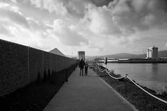 The Walk (strobebelfast) Tags: belfast northernireland 2018 titanicquarter blackwhite monochrome blackandwhite strobebelfast industrial industry port docks people clouds