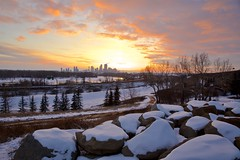 Sunset on the Rocks (John Andersen (JPAndersen images)) Tags: bowriver calgary city clouds pond reflections sky skyline spring sunset trees