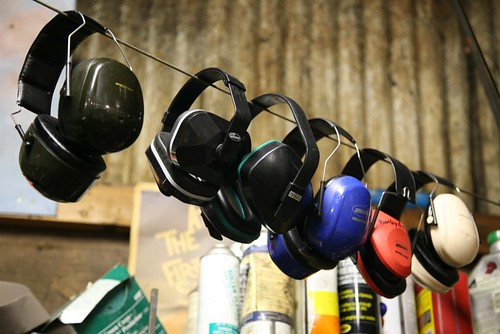 six slightly different industrial ear muffs strung on a clothes line, a number of unidentifiable aerosol bottles in the background