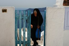 Santorini woman and blue door (tollen) Tags: black scarf hands dress memories santorini greece mediterraneansea vaccation aegeansea aegeanblue descendantoforiginalsettlers