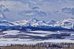 Blue Rockies Spring mood (John Andersen (JPAndersen images)) Tags: calgary clouds farm mountains pond reflections rockies sky skyline spring trees