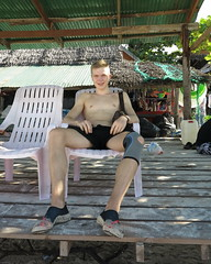 Respite From The Sun (Chris Hunkeler) Tags: kohkhainok khai เกาะไข่นอก speedo swimtrunk swimsuit young man seated sitting tropical thailand shirtless male teen lean fit sports knee brace wraparound sleeve openpatella satchel manpurse murse manshandbag malepurse watershoes aquasocks swimshoes