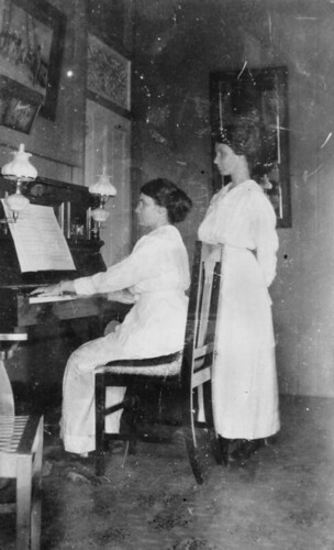A woman plays the piano at her home in Taringa, Brisbane, while her sister watches, 1916
