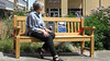 Woman sitting on Blackbox-av Talking Solar Powered Bench