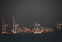 """a container ship lurks under massive cranes - moody fine art view of Le Havre across the Seine River from across the Seine River, Honfleur, Calvados, Normandy, France (grumpybaldprof) Tags: honfleur normandy normandie france calvados """"lehavre"""" """"laseine"""" river moody murk sharp """"fineart"""" ethereal striking artistic interpretation impressionist stylistic style contrast shadow bright dark white illuminated colour colourful container ship atmosphere cranes dock port marine maritime bassin bateau tones winter telephoto canon 70d """"canon70d"""" tamron 16300 16300mm """"tamron16300mmf3563diiivcpzdb016"""""""
