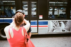 Wrong Hands - The Chicagoans (cpplunkett) Tags: couple kissing kiss streetphotography streetphoto urban streetcorner bus chicago advertisement juxtaposition ad colorst streetzen