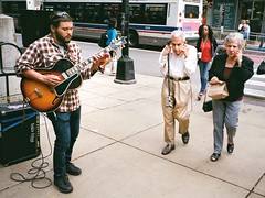 Ear Plugs - The Chicagoans (cpplunkett) Tags: theloop chicago downtown statestreet streetmusician guitar elderly oldman pluggingears streetphotography streetphoto thechicagoans 35mm film