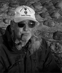 A MOMENT TO REFLECT (artspics_1) Tags: man pipe sunglasses beard cap baseballcap smoke smoking tobacco relaxing wall flintwall