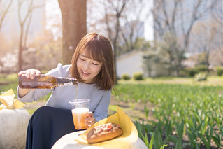 Young woman pouring beer outside for lunch