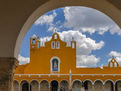 Under the arch (Adaptabilly) Tags: yucatán arcade stainedglass building izamal people mx clock lumixgx7 clouds mexico travel arch sky cross wall yellow bell architecture