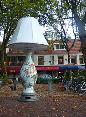 Seeing the Light. (jenichesney57) Tags: lamp delft holland square street shops panasoniclumixtz60 autumn leves trees buildings porcelain shadebikes car people rooftiles bunting benches wooden blue red orange yellow