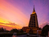 Wat Dhammamongkol Sunset (Matt Molloy) Tags: mattmolloy photography tall temple stupa sunset colourful clouds sky light beam bushes city buildings skyscrapers construction architecture watdhammamongkol phrakhanong bangkok thailand lovelife