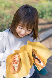 Young woman holding three pieces of hot dogs for lunch