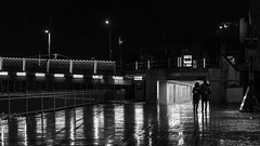 Bir şehri bırakmak (*) / Happy Birthday Orhan Veli! (Özgür Gürgey) Tags: 169 2017 50mm bw d750 darkcity galatabridge karaköy nikon orhanvelikanık evening lowlight people rain reflection street istanbul