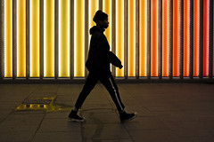 yellow light 154/156 (markfly1) Tags: london liverpool street city cityscape underground walkway tunnel passage red yellow orange black white contrast highlights vertical stripes colour color candid image woman walking stripe lines boots shoes stride d750 35mm analogue lens manual focus