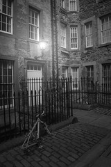 The wrong place to park a bike B&W (WISEBUYS21) Tags: bw blackandwhite edinburgh streetscene bike bicycle railings night lamp light doors flats tenements road cobbles old days spooky haunting times back time streets wisebuys21 special effects fx film work movie cinematic