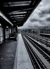 Waiting on a train (soboy5) Tags: trainstation platform subway mono bw monochrome clouds tracks nyc brooklyn bushwick leadinglines centralavenue subwaystation newyorkcity buildings diagonals architecture lines