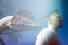 Man and Dinosaur Profile (Sean Anderson Media) Tags: sonya7sii nikon50mmf14g portrait style fashion colorflare fotodiox lensadapter nikontosony lightleak incameraeffect organiclightleak kenosha wisconsin model flare retro vintage filmlook vintagefilmlook retrofilmlook retrolook dinosaur dinosaurstatue profile sky dramatic weird