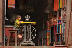 kid on sewingmachine (trying to catch up again !!!) Tags: child nepal nepali travel streetphotography streetlife sewingmachine clothesshop shop ivodedecker wahling candid cloth
